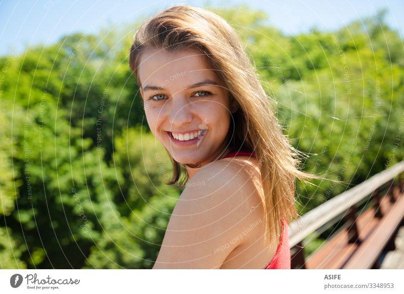 Porträt eines glücklichen, schönen Teenager-Mädchens, das an einem sonnigen Tag lächelt Lifestyle Freude Glück Gesicht Erholung Freizeit & Hobby Sommer Sonne