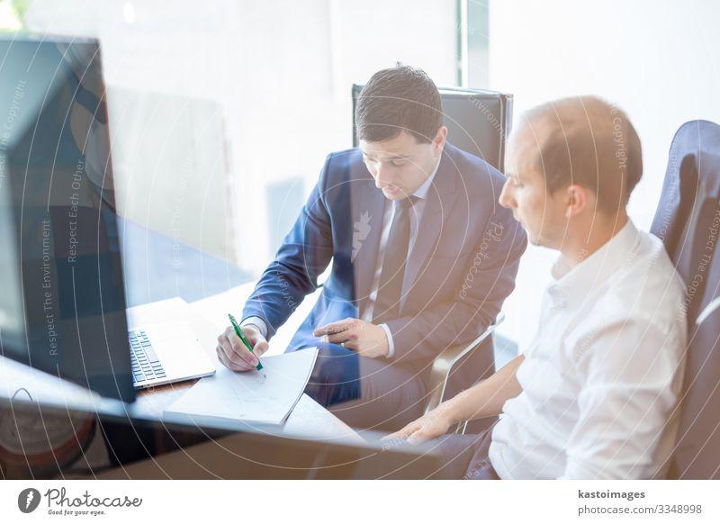 Bild von zwei Geschäftsleuten, die sich bei einem Treffen in einem modernen Handelsbüro über ein Bissigkeitsproblem unterhalten. Geschäftsleute sitzen im Sitzungssaal und besprechen den Geschäftsplan.