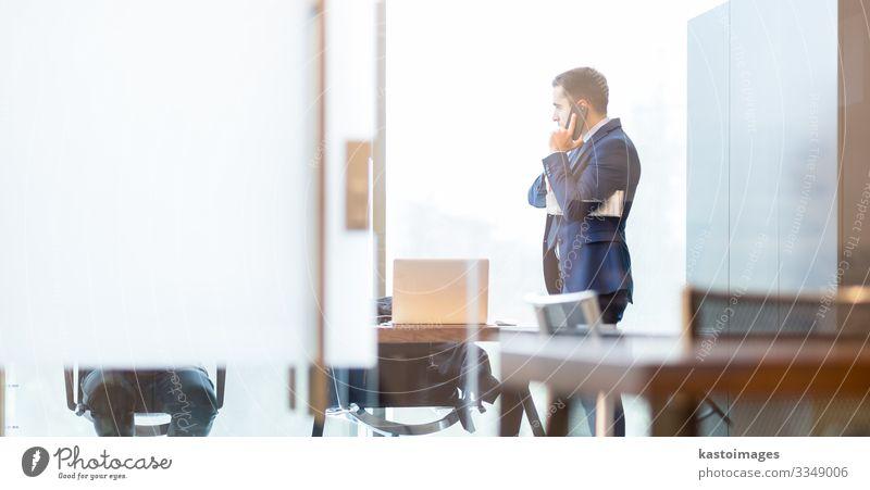 Ein Geschäftsmann, der mit dem Handy telefoniert und durch das Fenster schaut. elegant Schreibtisch Arbeit & Erwerbstätigkeit Beruf Arbeitsplatz Büro Business