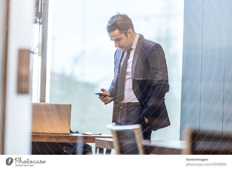 Geschäftsmann mit Blick auf das Smartphone im modernen Firmenbüro. elegant Schreibtisch Arbeit & Erwerbstätigkeit Beruf Arbeitsplatz Büro Business Unternehmen