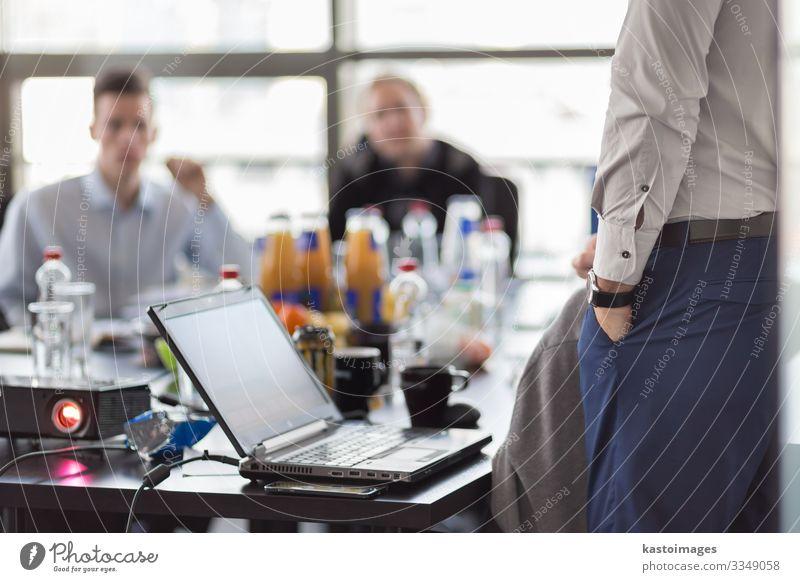 Geschäftsmann macht eine Präsentation im Büro. Geschäftsmann, der seinen Kollegen während einer Besprechung oder eines internen Geschäftstrainings eine Präsentation vorträgt. Rückansicht. Geschäft und Unternehmertum.