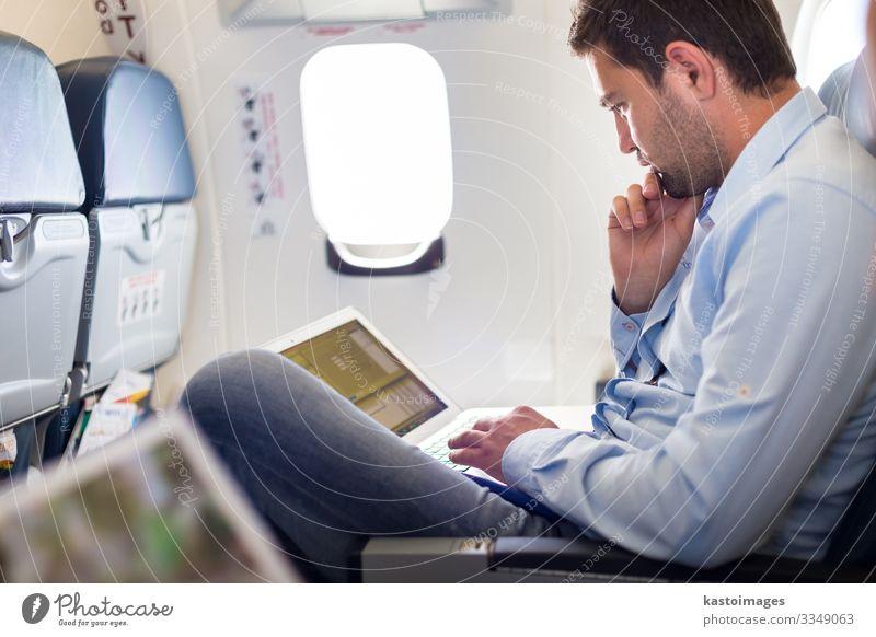 Geschäftsmann, der mit einem Laptop im Flugzeug arbeitet. Lifestyle lesen Ferien & Urlaub & Reisen Ausflug Arbeit & Erwerbstätigkeit Wirtschaft Business