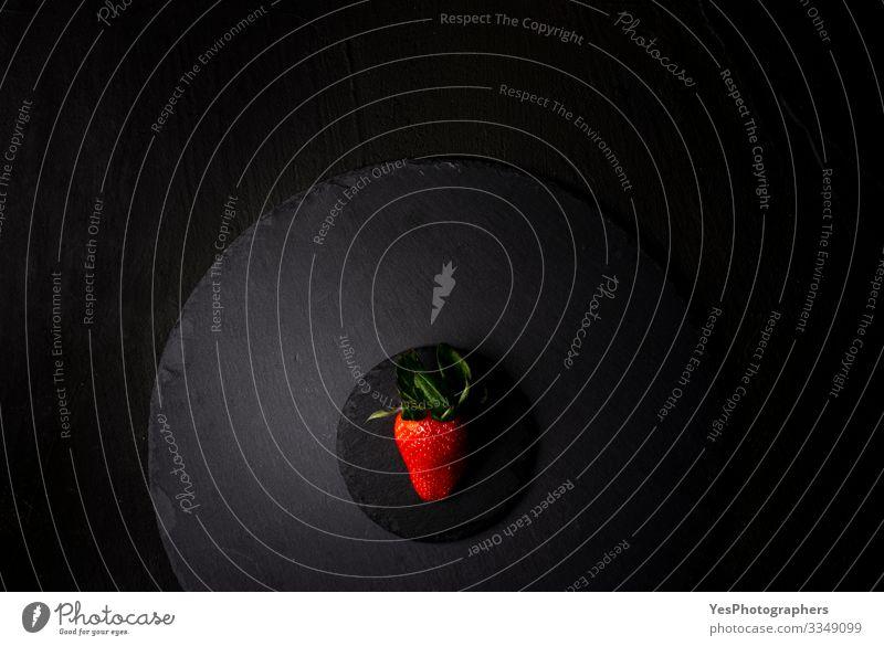 Eine einzelne Erdbeere auf einer schwarzen Granitplatte. Ansicht oben Frucht Dessert Bioprodukte Diät frisch lecker natürlich obere Ansicht Beeren Schwarzblech