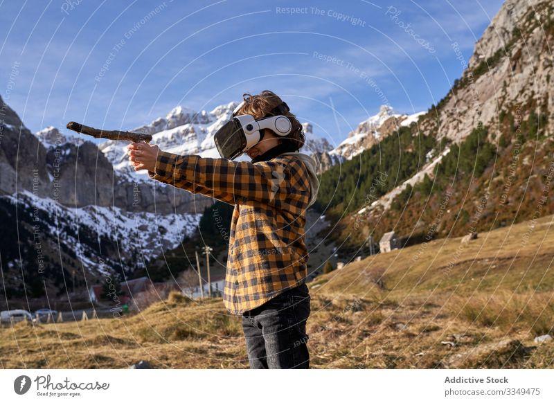 Auf Stein stehender Junge mit VR-Brille gegen Berg Natur Tal Berge u. Gebirge virtuell kleben Realität Headset modern Gerät Entertainment erkunden Gelände