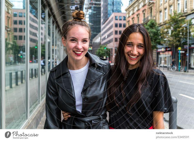 Porträt von zwei jungen Frauen, die Seite an Seite auf der Straße lächeln Lifestyle schön Erwachsene Jugendliche Fröhlichkeit Lebensfreude Liebe Junge Frauen