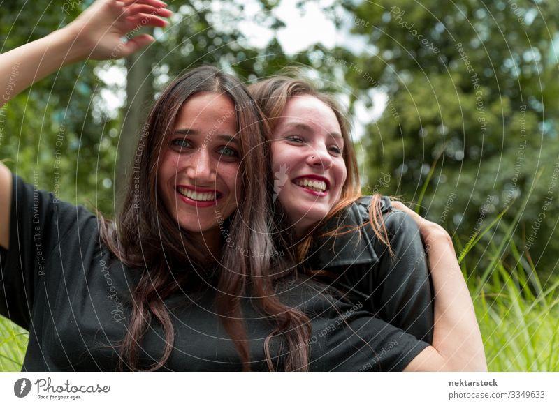 Mädchen aus dem Nahen Osten und dem Kaukasus umarmen und lächeln Freude schön Frau Erwachsene Freundschaft Jugendliche Natur Gras Lächeln Umarmen Fröhlichkeit