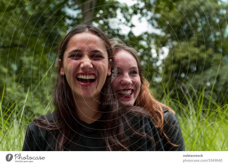 Zwei Freundinnen verschiedener Rassen lachen im Freien Freude schön Frau Erwachsene Freundschaft Jugendliche Natur Gras Park Umarmen Fröhlichkeit Zusammensein