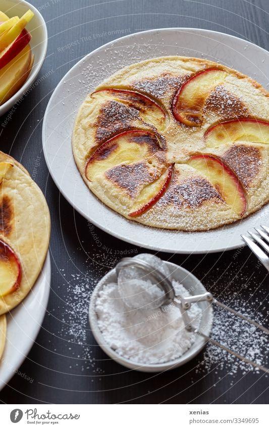 Pfannkuchen mit Apfel und Puderzucker auf weißem Teller Teigwaren Backwaren Süßwaren Apfelspalte Zucker Ernährung Bioprodukte Lebensmittel