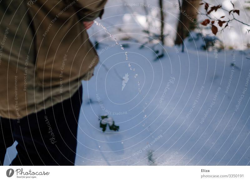 Ein Mann pinkelt in den Schnee pinkeln urinieren Wildpinkeln Pipi Strahl Urin Wasser lassen draußen Natur Wald Winter kalt
