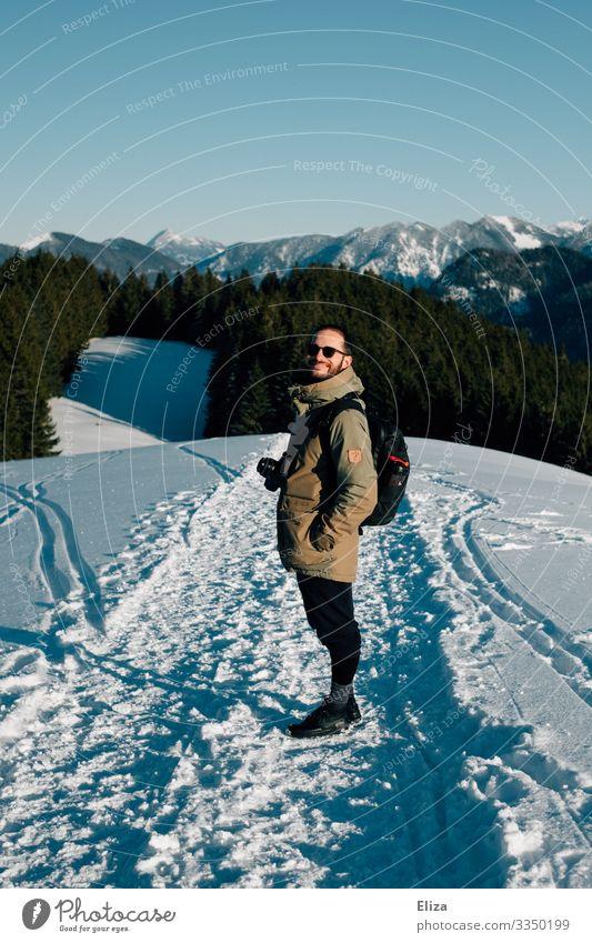 Ein Mann im Schnee auf einem Berg an einem sonnigen Tag mit Aussicht auf die Alpen. Wandern im Winter. Mensch Winterwanderung maskulin Junger Mann Jugendliche