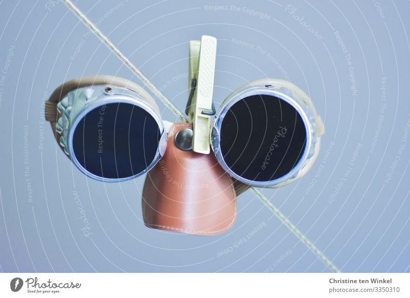 alte Gletscherbrille hängt an einer Wäscheleine Brille Schutzbrille Sonnenbrille Wäscheklammern hängen Blick authentisch Fröhlichkeit Originalität retro rund