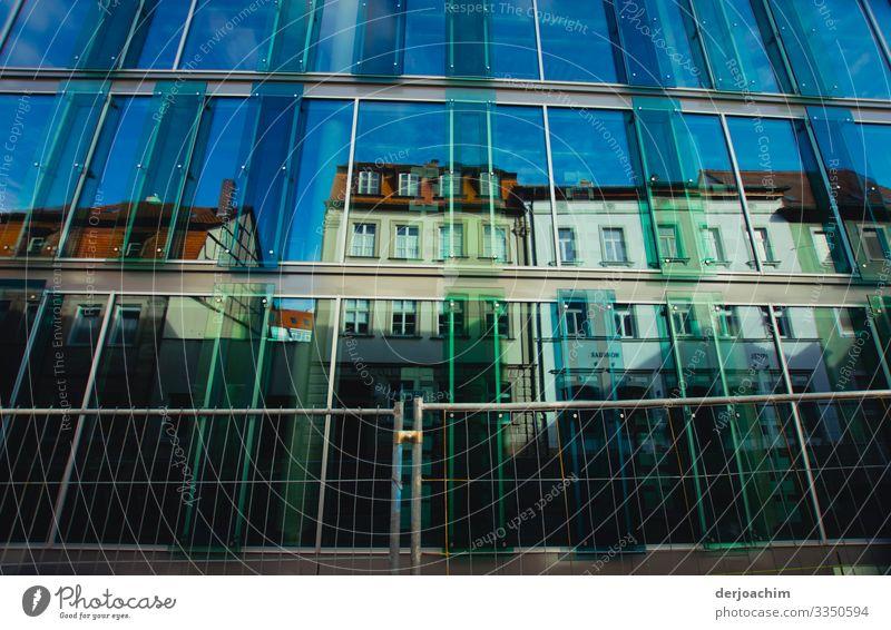 Häuserzeile mit verschiedenen Farben und einem blauen Himmel ,davor eine Glaswand. Reflexion & Spiegelung Wolken Sonne Licht Außenaufnahme sky reflection light