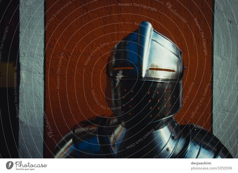 abgehoben / nicht mit der Rüstung. Eine Glänzende Ritterrüstung mit Helm. nur bis  im Schulterbereich zu sehen, vor einer roten Wand. Freude harmonisch Ausflug