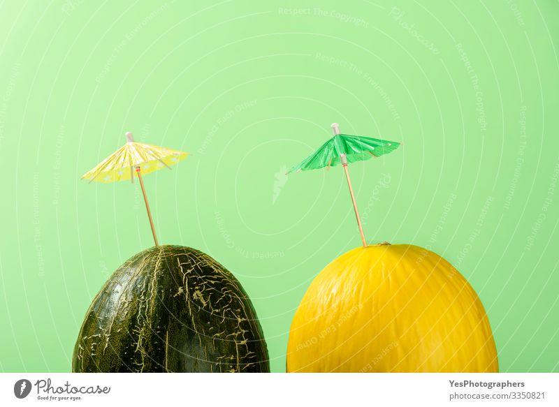 Zwei Melonen mit Cocktailschirm, Konzept für Sommermelonengetränke Frucht Dessert Bioprodukte lecker farbenfroh Entwurf Kürbisgewächse Diätnahrung