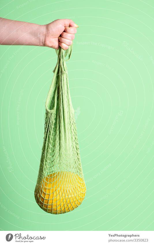 Gelbe Melone in wiederverwendbarer Netz-Einkaufstasche Frucht Dessert Bioprodukte Diät kaufen Gesunde Ernährung feminin Hand grün Früchte kaufen farbenfroh