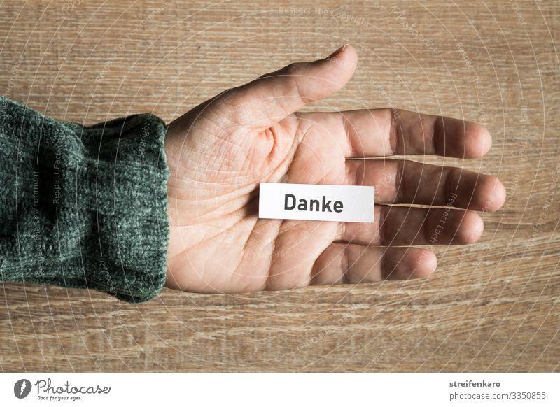 Zettel mit Schriftzug DANKE liegt in geöffneter Handfläche vor Holzhintergrund Erfolg sprechen Team Mensch Papier Schriftzeichen Kommunizieren Freundlichkeit