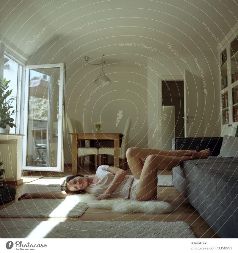 Junge Frau liegt im Wohnzimmer am Sofa und lächelt Lifestyle Freude schön Wohlgefühl Häusliches Leben Wohnung Möbel Tisch Fenster Jugendliche Erwachsene Beine