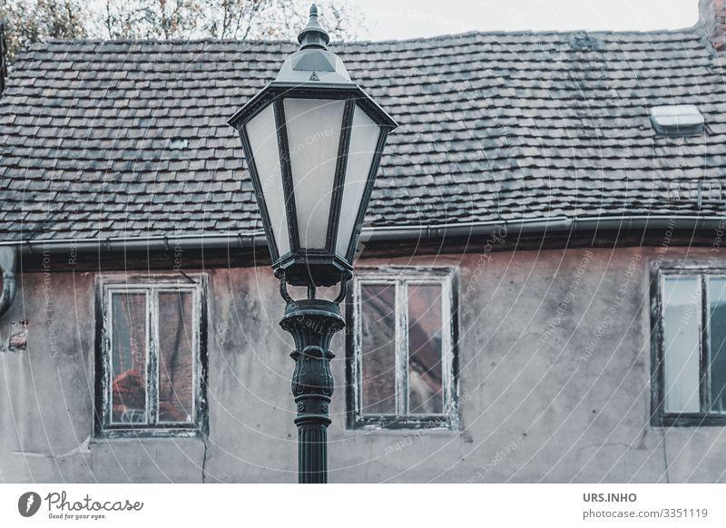 Straßenlaterne vor einem alten Haus Dorf Menschenleer Gebäude Mauer Wand Fassade Fenster Dach Armut hässlich retro braun grau schwarz Senior Verfall