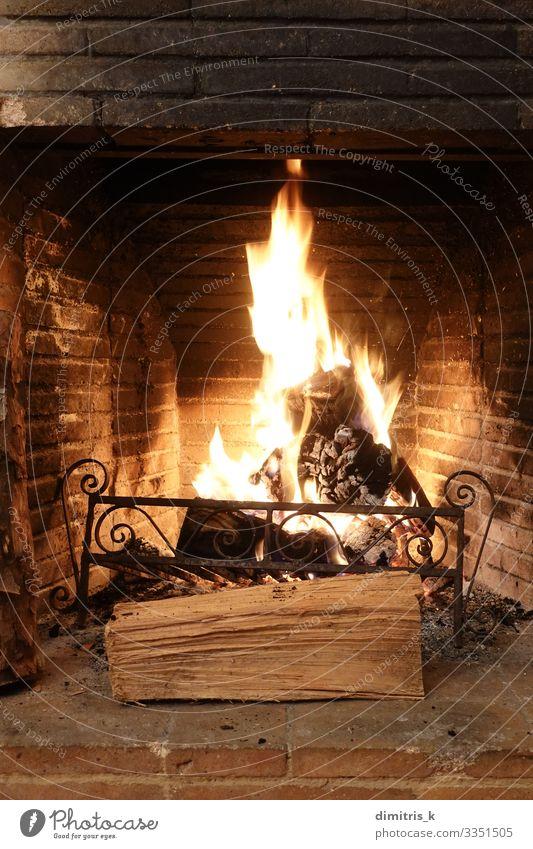 Feuer in einem alten Kamin mit verkohlten Ziegeln brennen Winter Metall Backstein dreckig schwarz Feuerstelle Holz brennend Flamme erwärmen Herd Brandasche