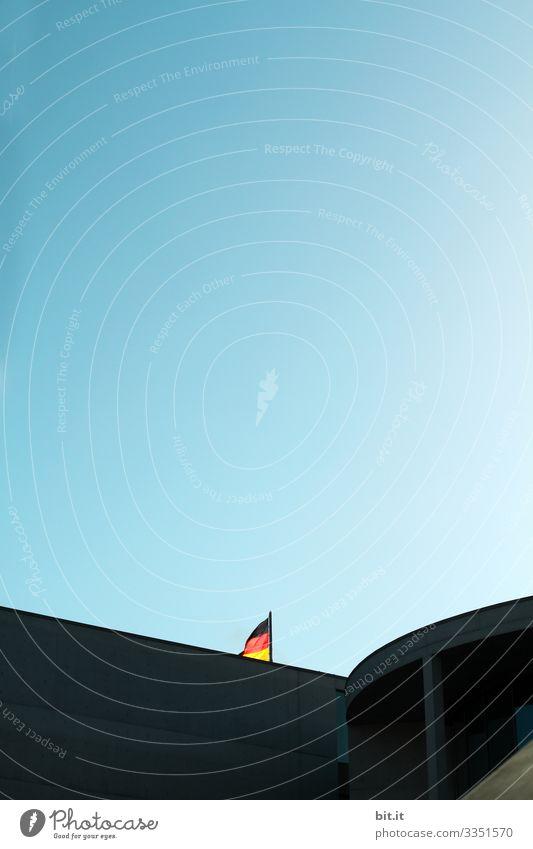 Fahne; Flagge von Deutschland an einem Mast, bei blauem Himmel im Regierungsviertel in Berlin, hinter einem Gebäude versteckt, im Sommer bei einem Ausflug während dem Urlaub in der Hauptstadt.