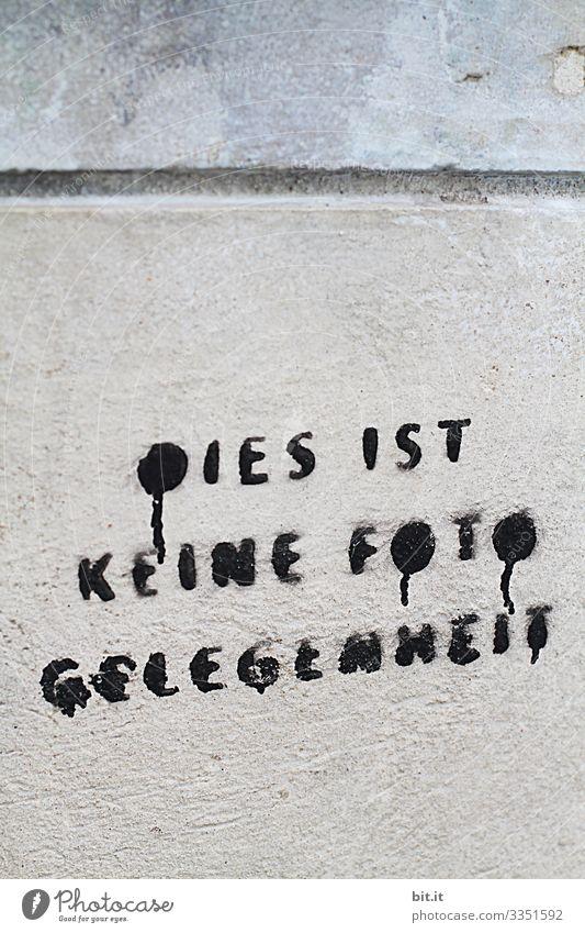 Schriftzug: Dies ist keine Fotogelegenheit, steht gesprayt, gemalt in schwarzen Buchstaben auf einer Wand aus Stein, eines Hauses geschrieben. Vorsicht, Verbot zu Fotografieren, als Hinweis. Fotoverbot.