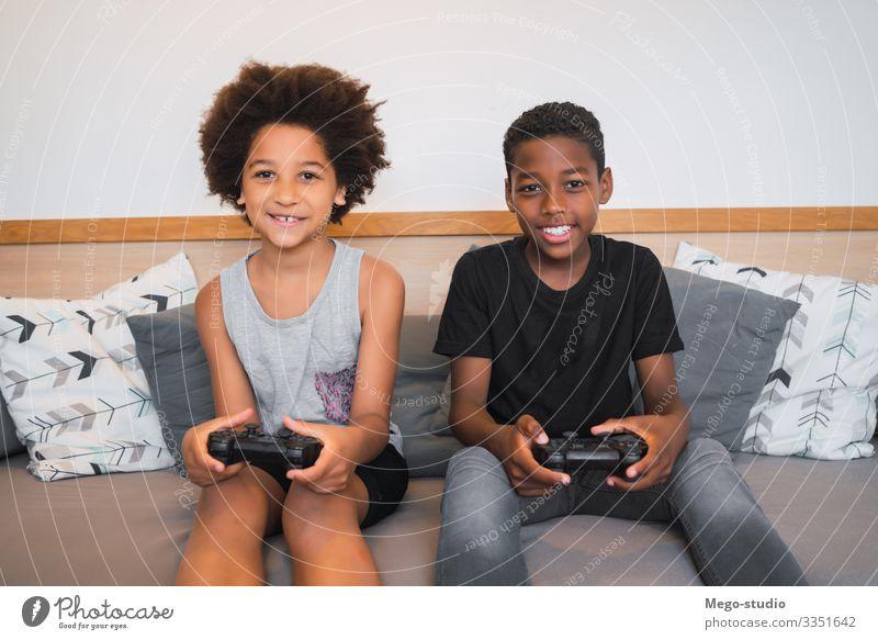 Zwei Brüder spielen zu Hause Videospiele. Lifestyle Freude Glück Freizeit & Hobby Spielen Sofa Entertainment Kind Technik & Technologie Mensch Junge