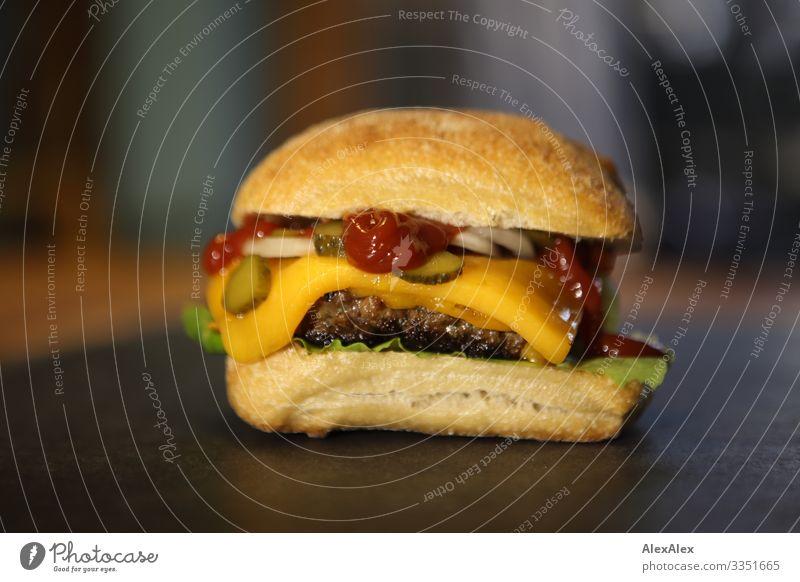 Cheeseburger- Sandwich mit Brötchen Lebensmittel Fleisch Salat Salatbeilage Teigwaren Backwaren Fastfood Käse Salatblatt Ketchup Zwiebel Gurkenscheibe