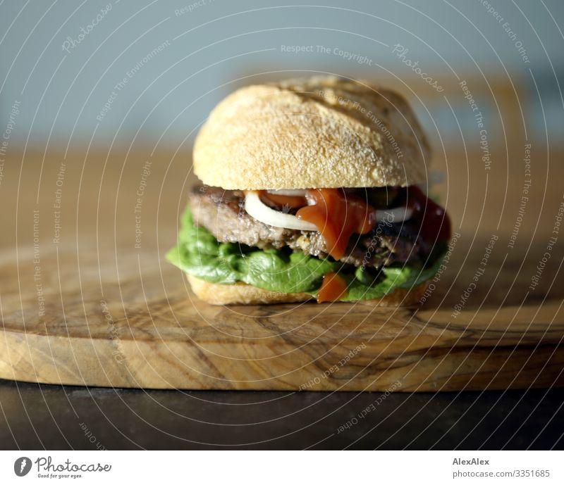 Hamburger- Sandwich mit Brötchen Lebensmittel Fleisch Salat Salatbeilage Teigwaren Backwaren Belegtes Brot Zwiebel Hackfleisch Beef Rindfleisch Holzbrett