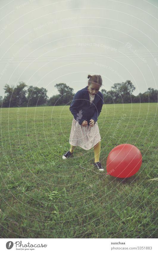 mädchen mit einem roten luftballon auf einer wiese Kind Mädchen Kindheit Wiese Luftballon spielen altmodisch retro Außenaufnahme Gras Umwelt Feld Freude