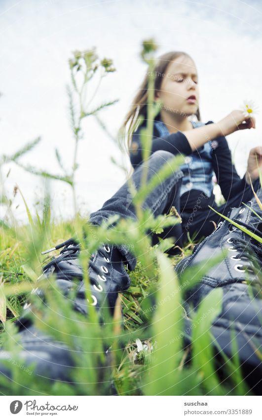 mädchen auf frühlingswiese mit schuhen im vordergrund Mädchen Kind Kindheit Frühling Wiese Gras Grashalm sitzen Blume wilde Kamille Stängel Perspektive Schuhe