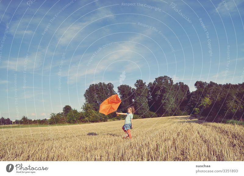 kind steht auf dem strohacker und hält einen kaputten regenschirm gegen den wind Kind Mädchen Acker Strohacker Getreidefeld Sommer Landschaft Natur Regenschirm