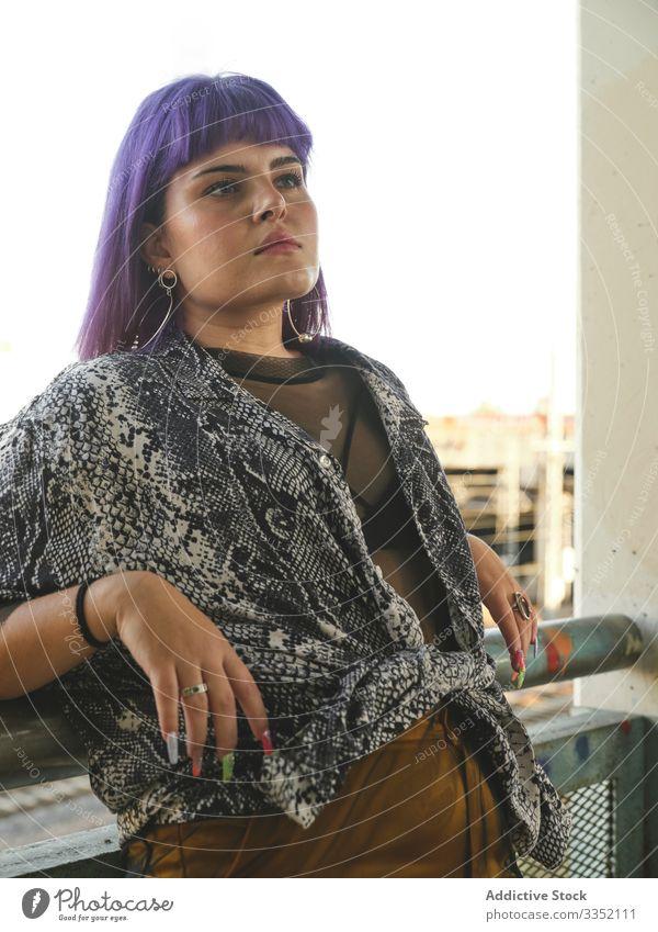 Frau mit lilafarbenen Haaren lehnt auf Metallzaun und schaut weg stylisch urban purpur Frisur Konstruktion glänzend Struktur Revier selbstbewusst Mode jung Stil