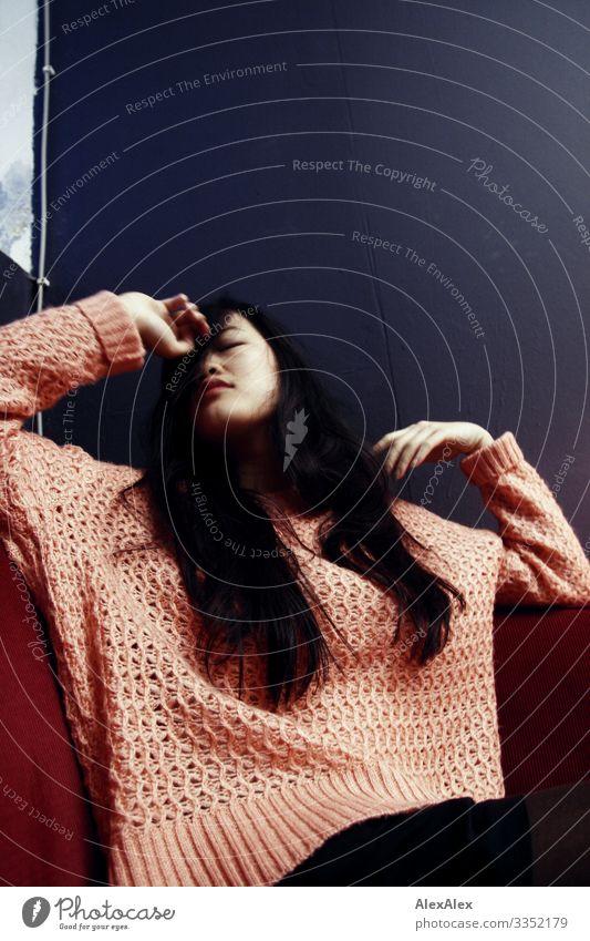 Portrait einer jungen Frau auf einem Sofa Stil schön Raum Lounge Junge Frau Jugendliche 18-30 Jahre Erwachsene Pullover schwarzhaarig langhaarig Beton Gefühle