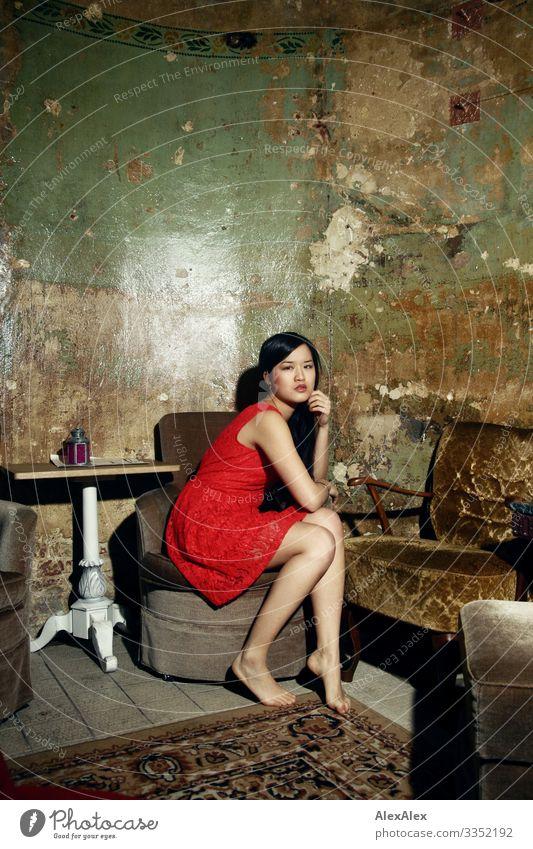 Junge Frau in rotem Kleid auf einem Sessel Stil Freude schön Leben Tisch Raum Wohnzimmer Jugendliche Beine 18-30 Jahre Erwachsene Barfuß schwarzhaarig