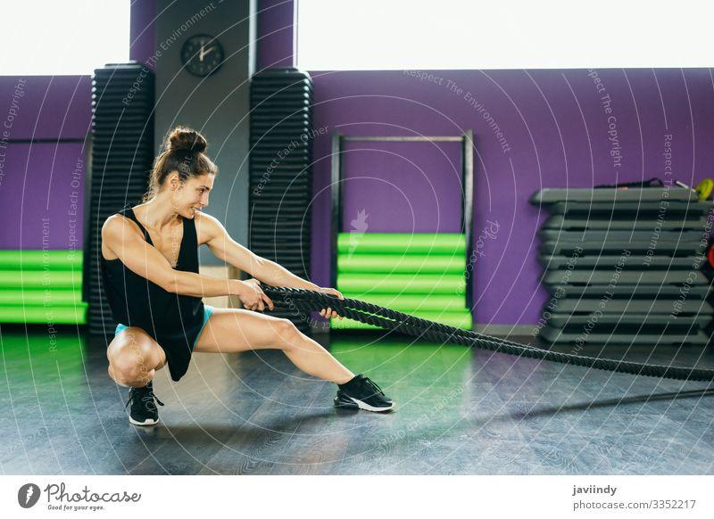 Junge und sportliche Frau, die Trainingsseile in einer Turnhalle benutzt. Lifestyle Körperpflege Wellness Club Disco Sport Seil Mensch feminin Junge Frau