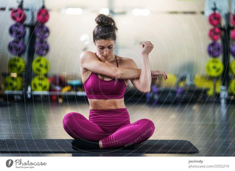 Junge Frau macht Dehnungsübungen auf einer Yogamatte im Fitnessstudio Lifestyle Körperpflege Wellness Club Disco Sport Mensch feminin Erwachsene Jugendliche