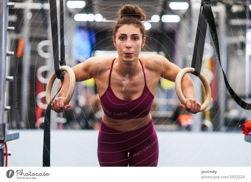 Athletische Frau bei Klimmzugübungen in den Gymnastikringen Lifestyle schön Körper Club Disco Sport Mensch feminin Junge Frau Jugendliche Erwachsene Arme 1