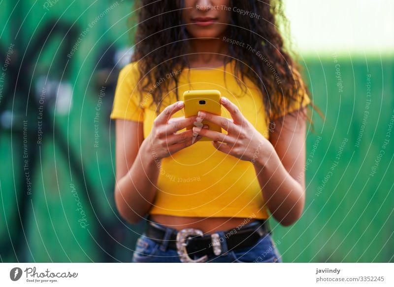 Junge arabische Frau geht auf der Straße mit ihrem Smartphone Lifestyle Stil Glück schön Haare & Frisuren Gesicht Telefon PDA Technik & Technologie Mensch