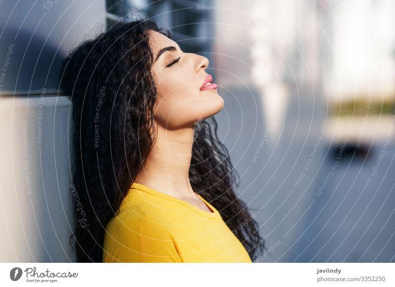 Junge arabische Frau mit geschlossenen Augen und mit dem Kopf an die Wand gelehnt auf der Straße. Lifestyle Stil schön Haare & Frisuren Schminke Sonne Mensch
