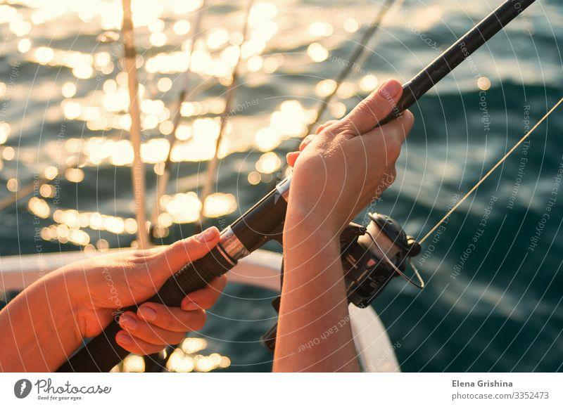 Weibliche Hände halten eine Angelrute zum Fischen. Lifestyle Erholung Freizeit & Hobby Angeln Ferien & Urlaub & Reisen Ausflug Meer Entertainment Frau