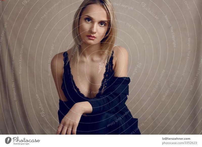 Sexy blonde Frau in einem schwarzen Spitzenoutfit schön Gesicht feminin Erwachsene 1 Mensch 18-30 Jahre Jugendliche Jacke Unterwäsche sitzen dünn attraktiv
