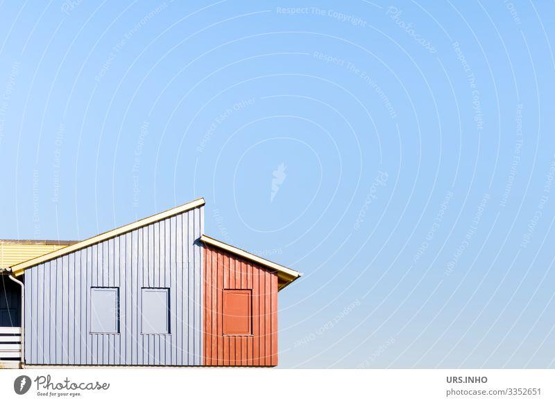 Holzhaus mit einem zweistufigen Pultdach vor blauem Hintergrund und viel Textfreiraum Himmel Haus Gebäude Fassade Fenster Dach Dachrinne authentisch schön gelb