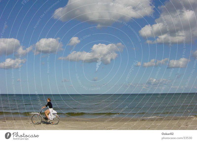 Fahrrad am Strand Frau Meer Wolken
