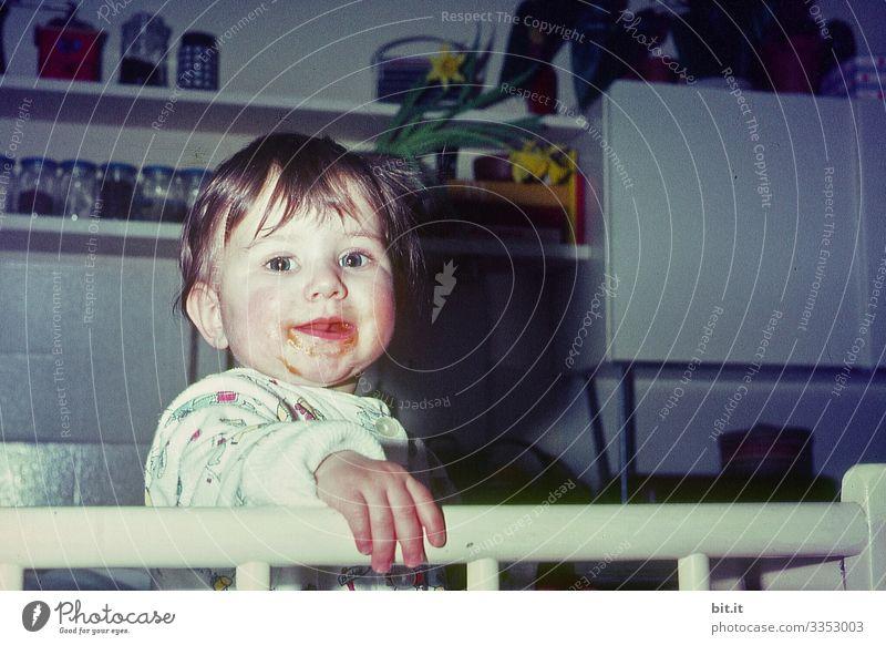 Kleines Mädchen in den 60er Jahren, steht im Laufstall in der Küche und freut sich mit verschmierten Mund, über den Brei zum Essen, und lächelt, frech, glücklich, fröhlich, verschmitzt in die Kamera.