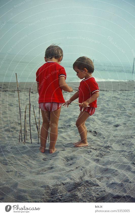 Zwei kleine Mädchen im Partnerlook, spielen am Strand, bauen mit Stöcken einen Zaun und lauschen dem Meer zu. Kindererziehung Freiheit Spielen Glück Natur