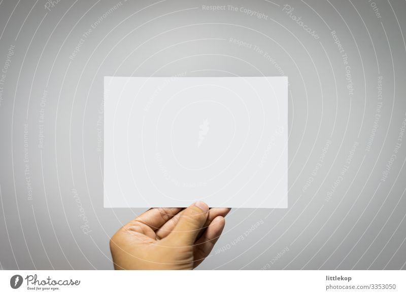 Weiße leere Postkarte auf grauem Hintergrund in der Hand haltend Büro Papier weiß altehrwürdig ruhend Plakat grauer Hintergrund vereinzelt Mitteilung Raum Gruß