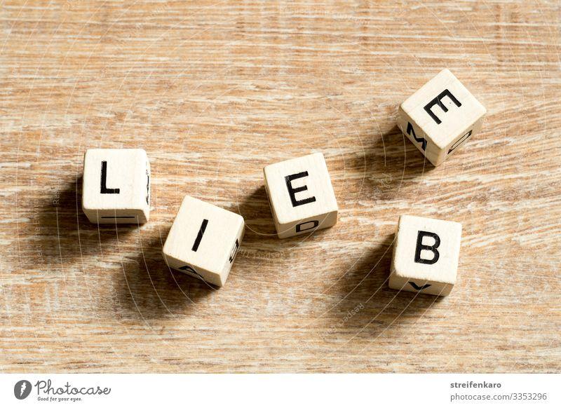 Holzwürfel mit Buchstaben bilden den Schriftzug LIEBE auf Holzuntergrund Freude Glück Paar Partner Leben Würfel Schriftzeichen Liebe Gefühle Lebensfreude