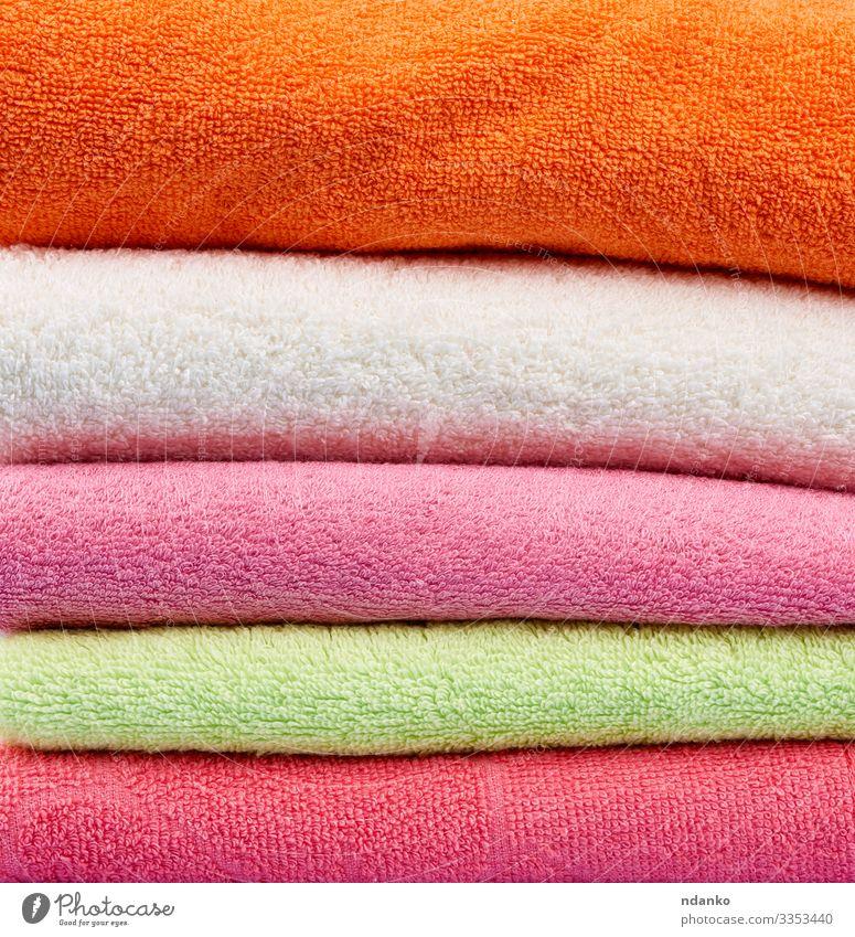 gefaltete Handtücher aus farbigem Baumwollfrottee Lifestyle Design Körper Erholung Spa Massage frisch modern neu Sauberkeit weich grün rosa weiß Farbe Textil