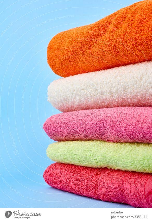 Stapel gefaltete Handtücher aus farbigem Baumwollfrottee Lifestyle Design Körper Erholung Spa Massage Stoff frisch modern neu Sauberkeit weich blau grün rosa