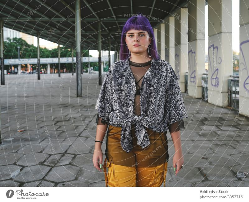 Frau mit violettem Haar schaut in die Kamera stylisch urban purpur Frisur Konstruktion glänzend Struktur Revier selbstbewusst Mode jung Stil Model Straße